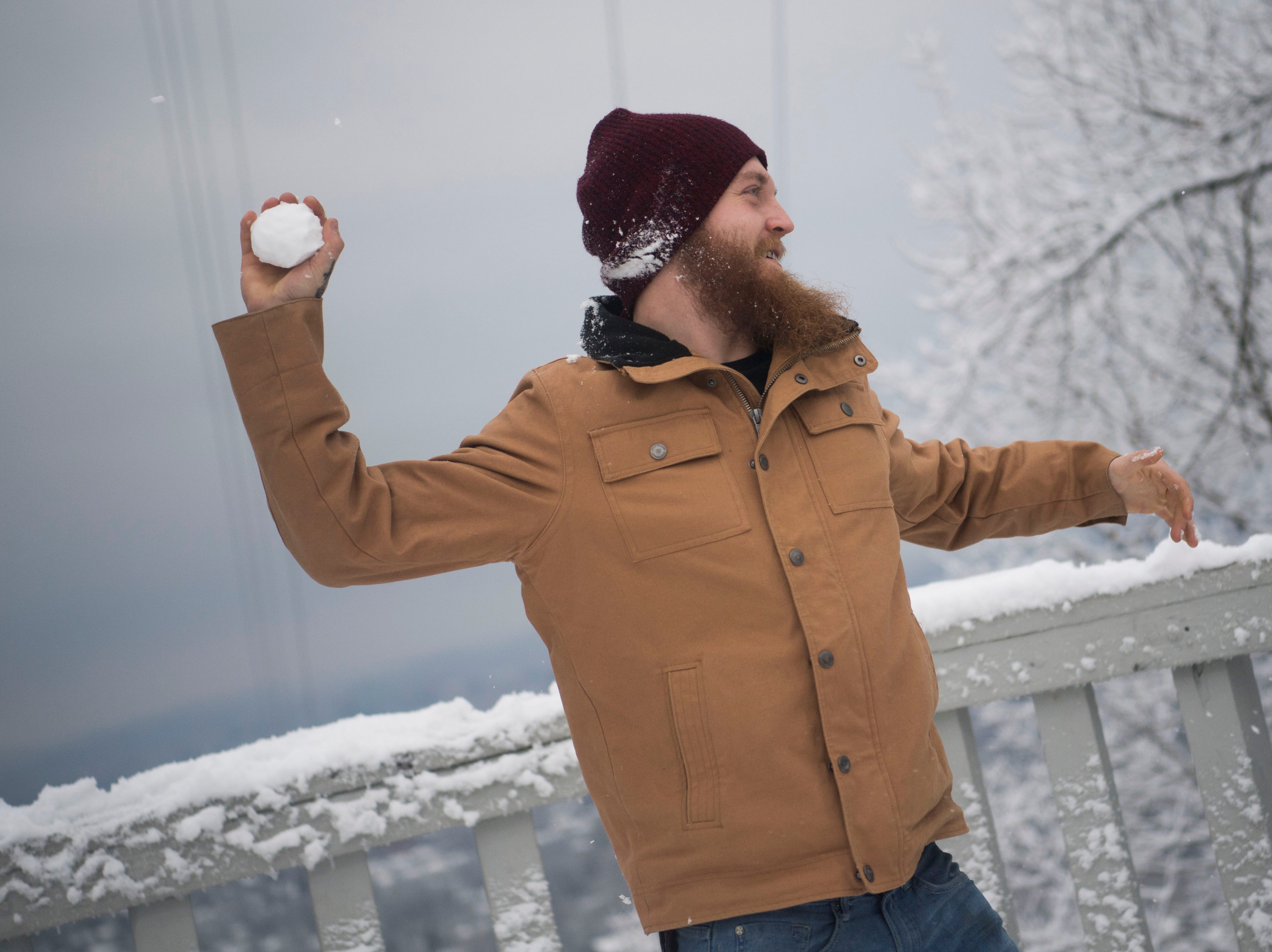 Austin Atkins winds up to throw a snowball at his brother on top of Sharps Ridge in North Knoxville Tuesday, Jan 29, 2019. The Knoxville area received about an inch of snow.