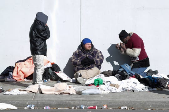 The homeless deal with the dropping temperatures under a viaduct Tuesday on Jefferson Street.