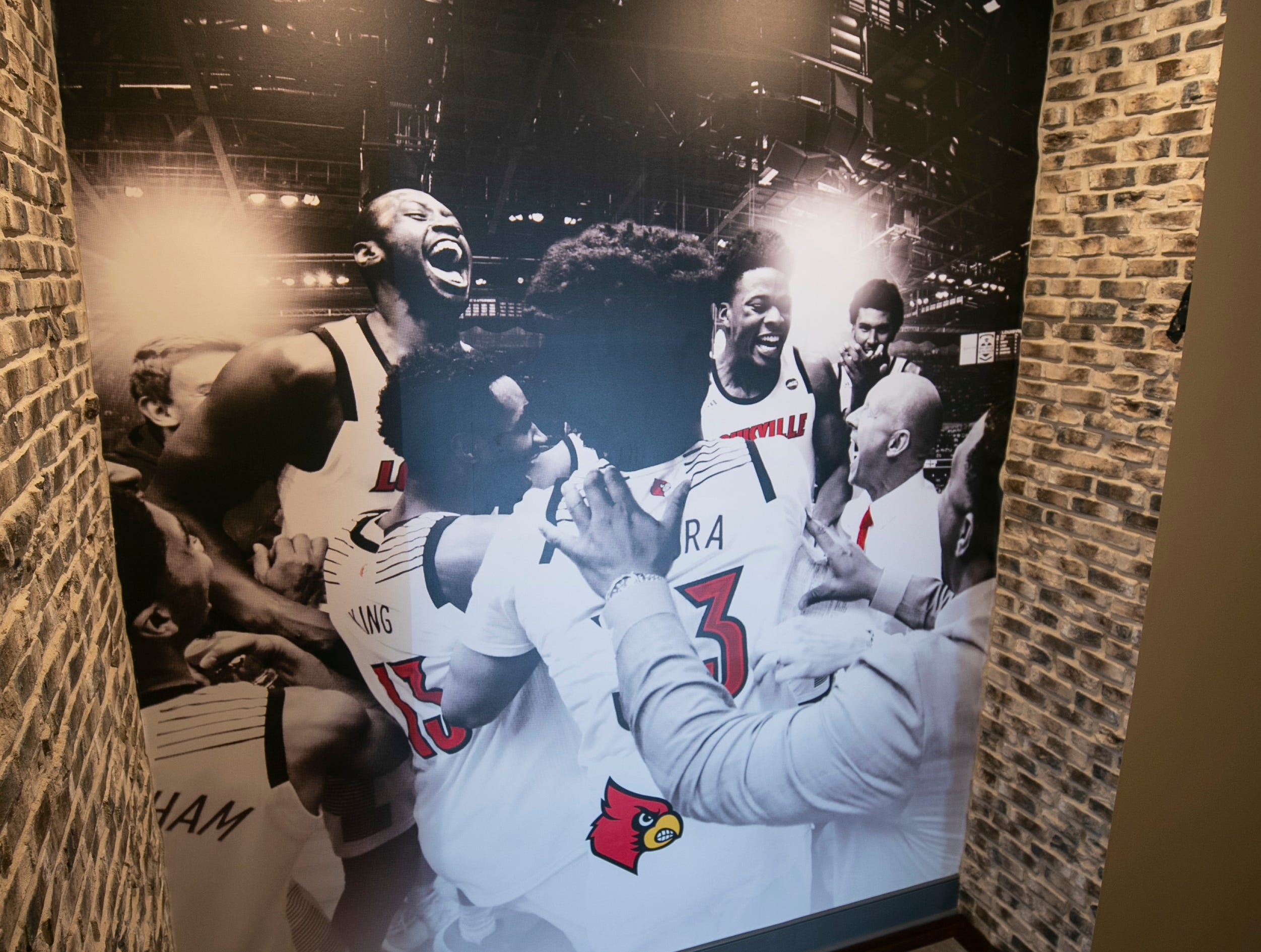 The stairs to the basement of the Mack home has homages to the Louisville basketball team, from a jubilation scene of Chris Mack with his players to a large L logo.