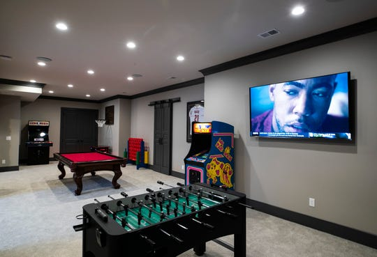The basement of the Mack home has vintage arcade games such as Mrs. Pac Man, NBA Jam and a pool table -- in red felt. There's also a wall-size photo of the KFC Yum! Center.