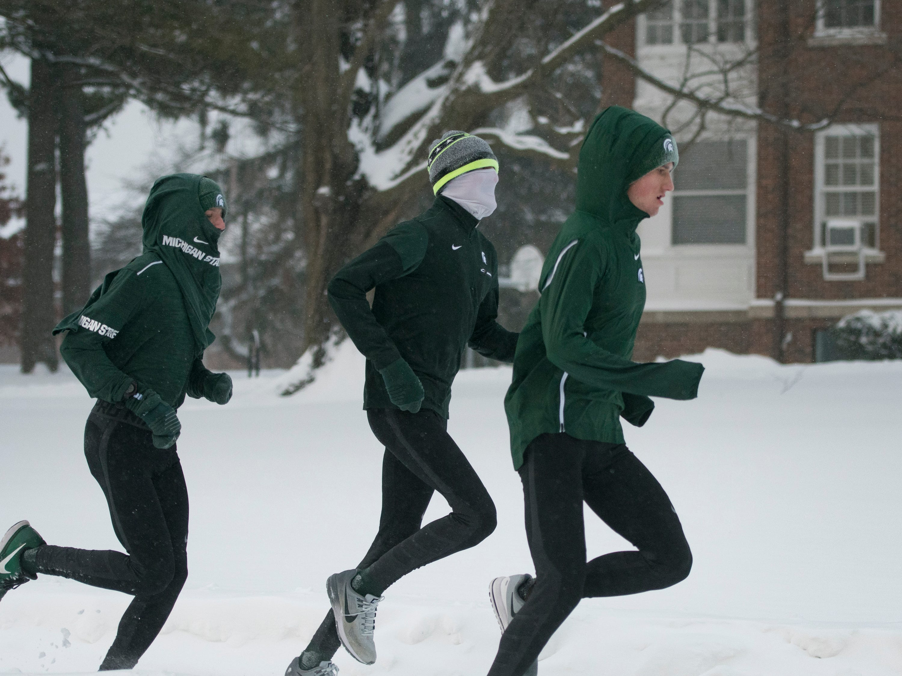 Despite sub-zero windchills, three run down Grand River Ave. on the campus of Michigan State University Tuesday, Jan. 29, 2019, in East Lansing, Michigan.  MSU canceled class Wednesday and Thursday and is lowering the temperatures in some buildings and serving a simpler menu in its dining halls in light of the state's energy emergency.