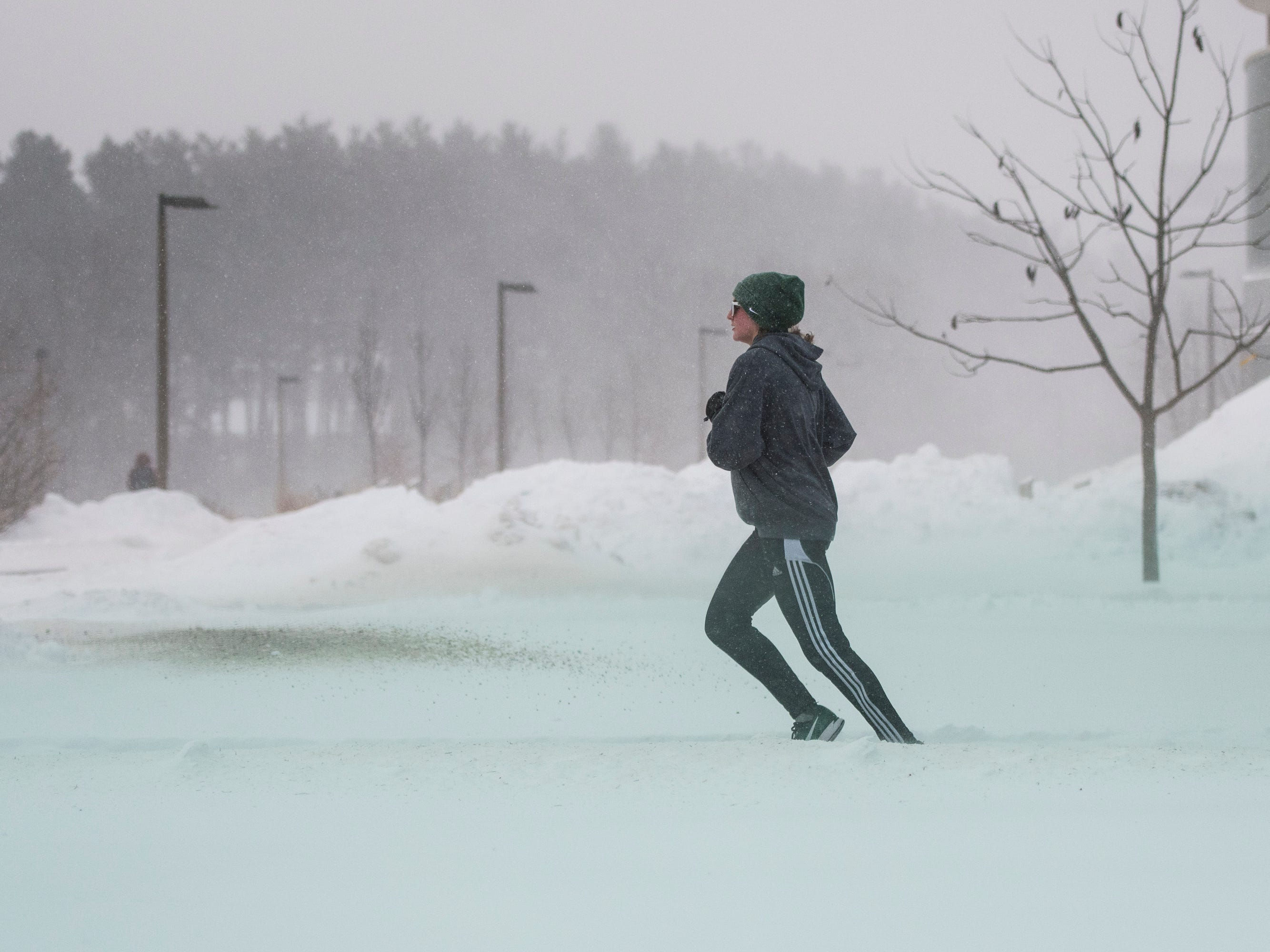 Despite sub-zero windchills, a woman runs across the campus of Michigan State University Tuesday, Jan. 29, 2019, in East Lansing, Michigan.  MSU has called off classes tommorow due to bitter temperatures.  [USA Today Network/Matthew Dae Smith/Lansing State Journal]