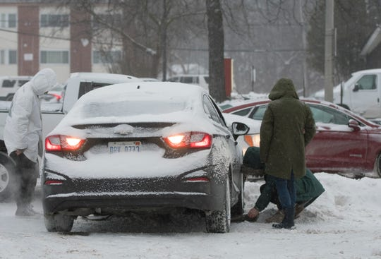 People try to get a car out of a snowbank Tuesday afternoon, Jan. 29, 2019, on Grand River Ave. in East Lansing, Michigan [Matthew Dae Smith/USA Today Network/Lansing State Journal]