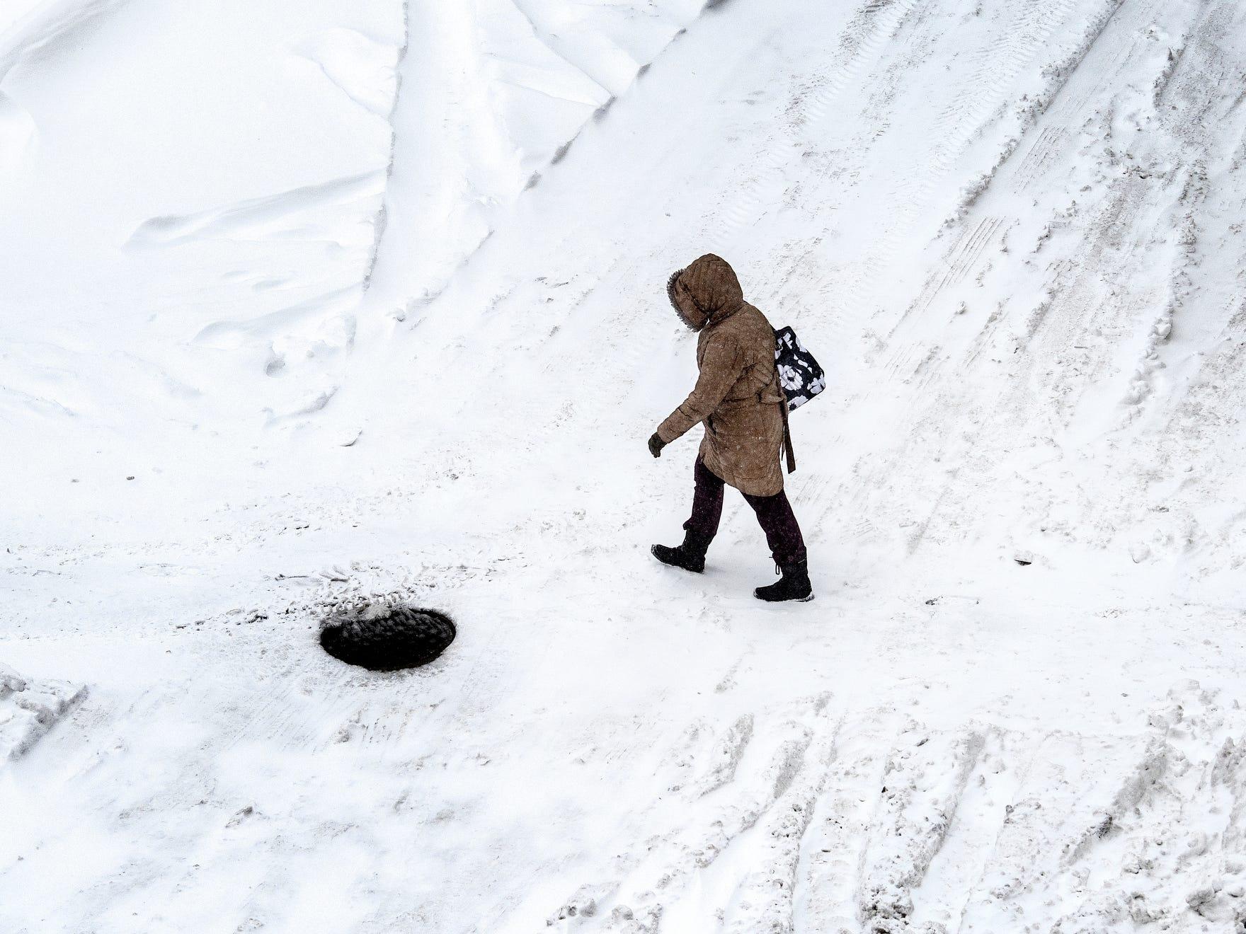 A pedestrian walks along Washtenaw Street in downtown Lansing on Tuesday, Jan. 29, 2019.