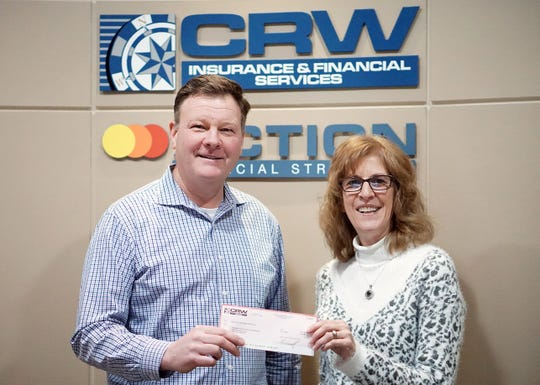 Jane Pribek, treasurer/bowling coach for the Manitowoc Miracles Special Olympics, accepts a donation check from Scott Wink of CRW Insurance.