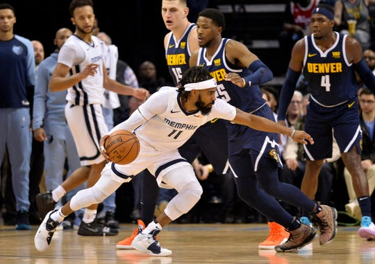 Memphis Grizzlies guard Mike Conley (11) handles the ball against Denver Nuggets guard Malik Beasley (25) in the first half of an NBA basketball game Monday, Jan. 28, 2019, in Memphis, Tenn. (AP Photo/Brandon Dill)