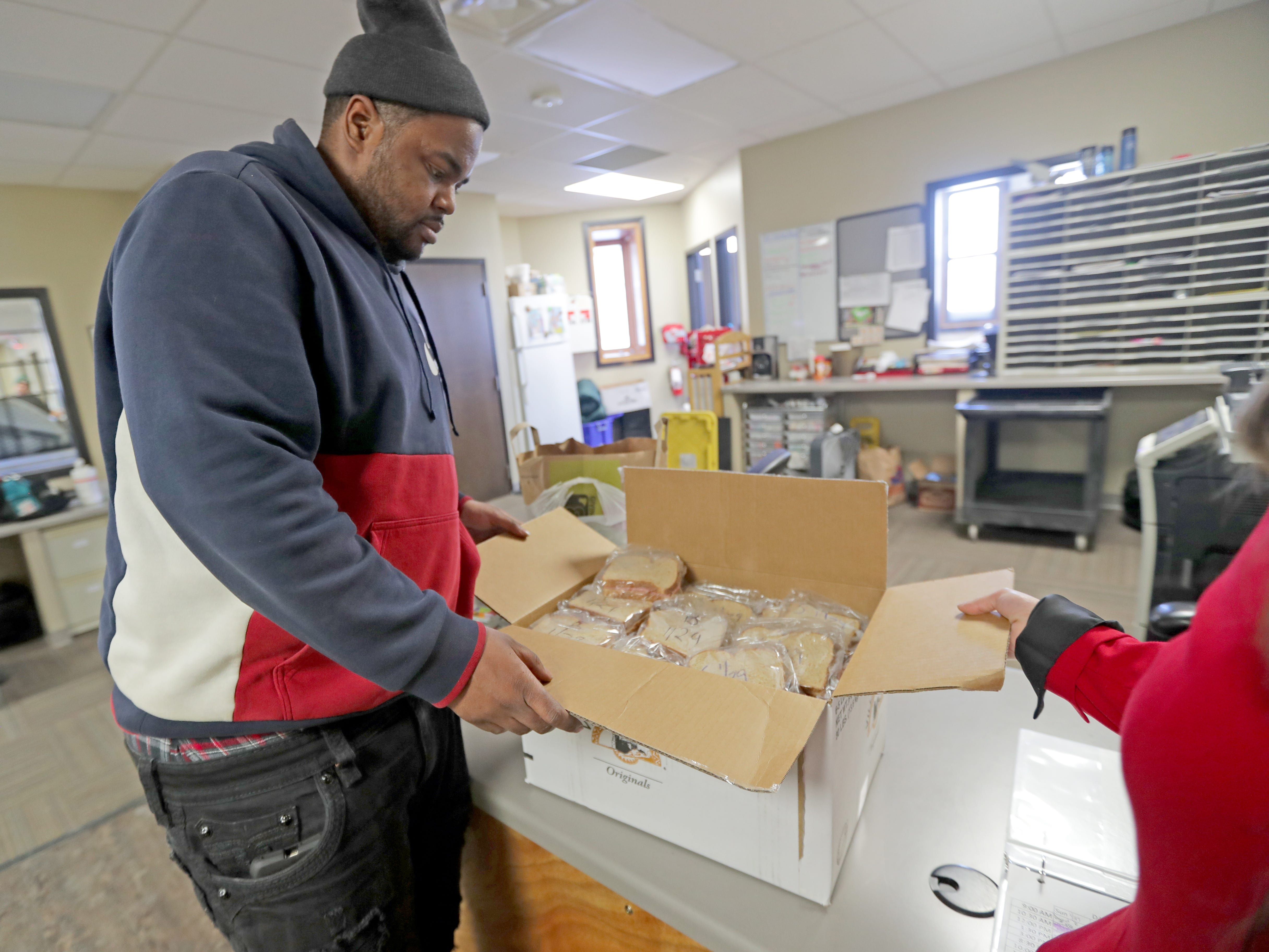 Guest House of Milwaukee employee William Love gets sandwiches ready for  those who need it at the facility on North 13th Street in Milwaukee.