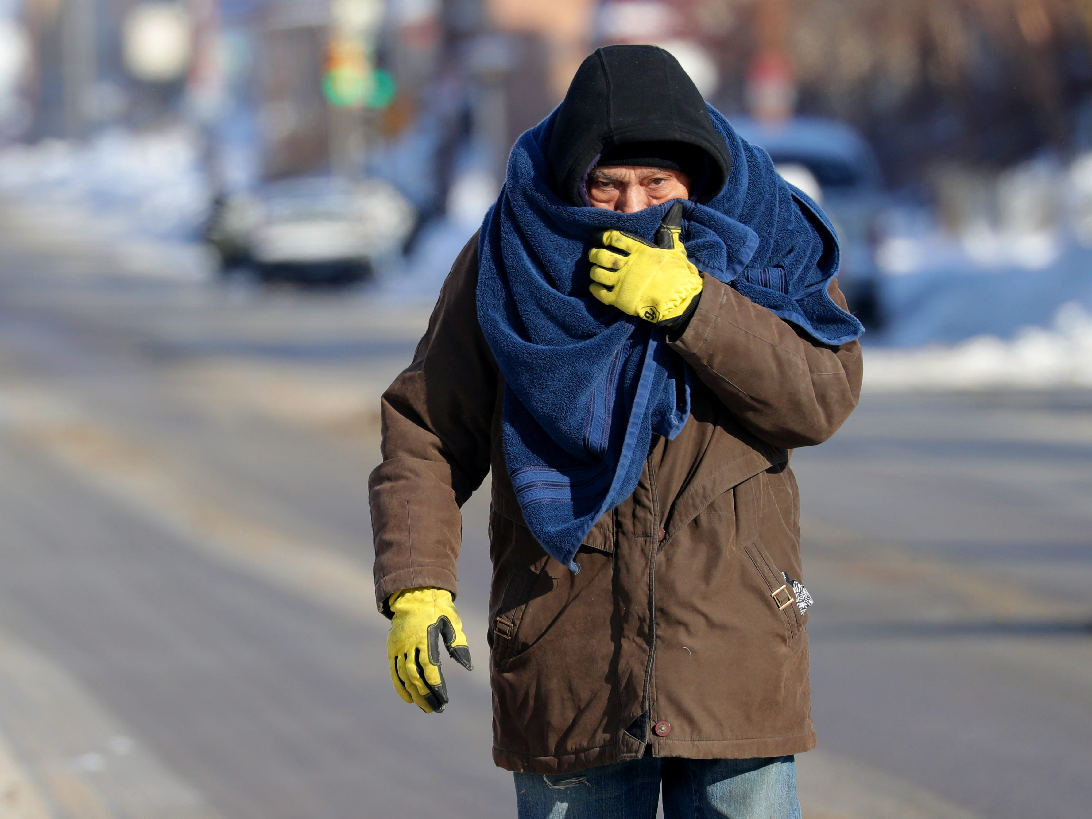 A man shields his face from the cold as he walks along North 27th Street just north of West Center Street in Milwaukee.