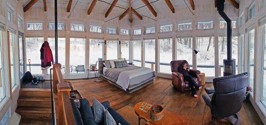 Carol Lewis relaxes in one of two recliners next to a Scandinavian stove in the Meadow House at Candlewood Cabins near Richland Center. The house's main level has glass-paneled walls, a queen bed and a couch.