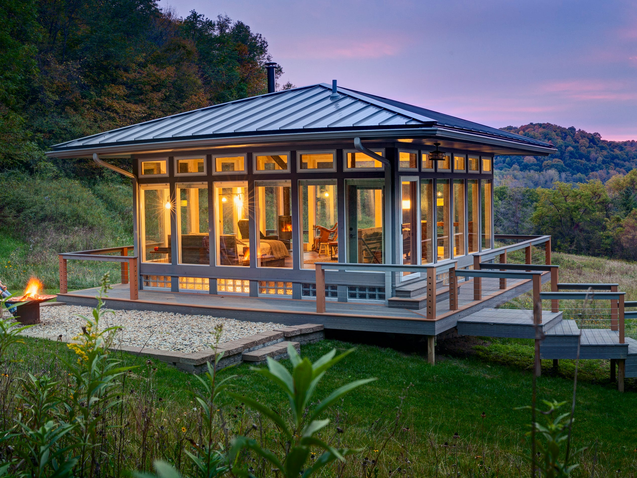 The Meadow House at Candlewood Cabins features four walls of glass panels for taking in views of the surrounding Driftless Area hills. A fire pit provides a spot for enjoying those views outside.