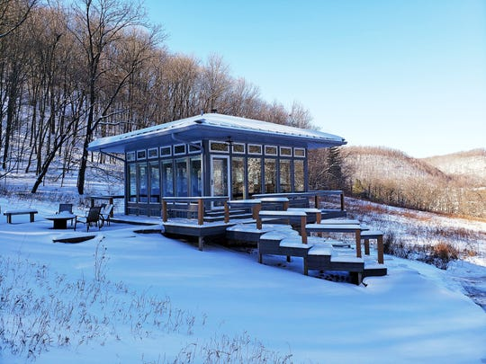 The Meadow House at Candlewood Cabins features four walls of glass panels for taking in views of the surrounding Driftless Area hills in any season.