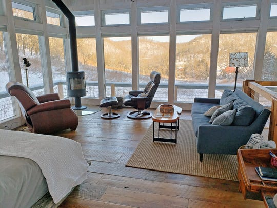 The Meadow House at Candlewood Cabins features four walls of glass panels for taking in views of the surrounding Driftless Area hills in any season. Rustic-chic touches like a reclaimed barn wood floor add to the house's coziness.