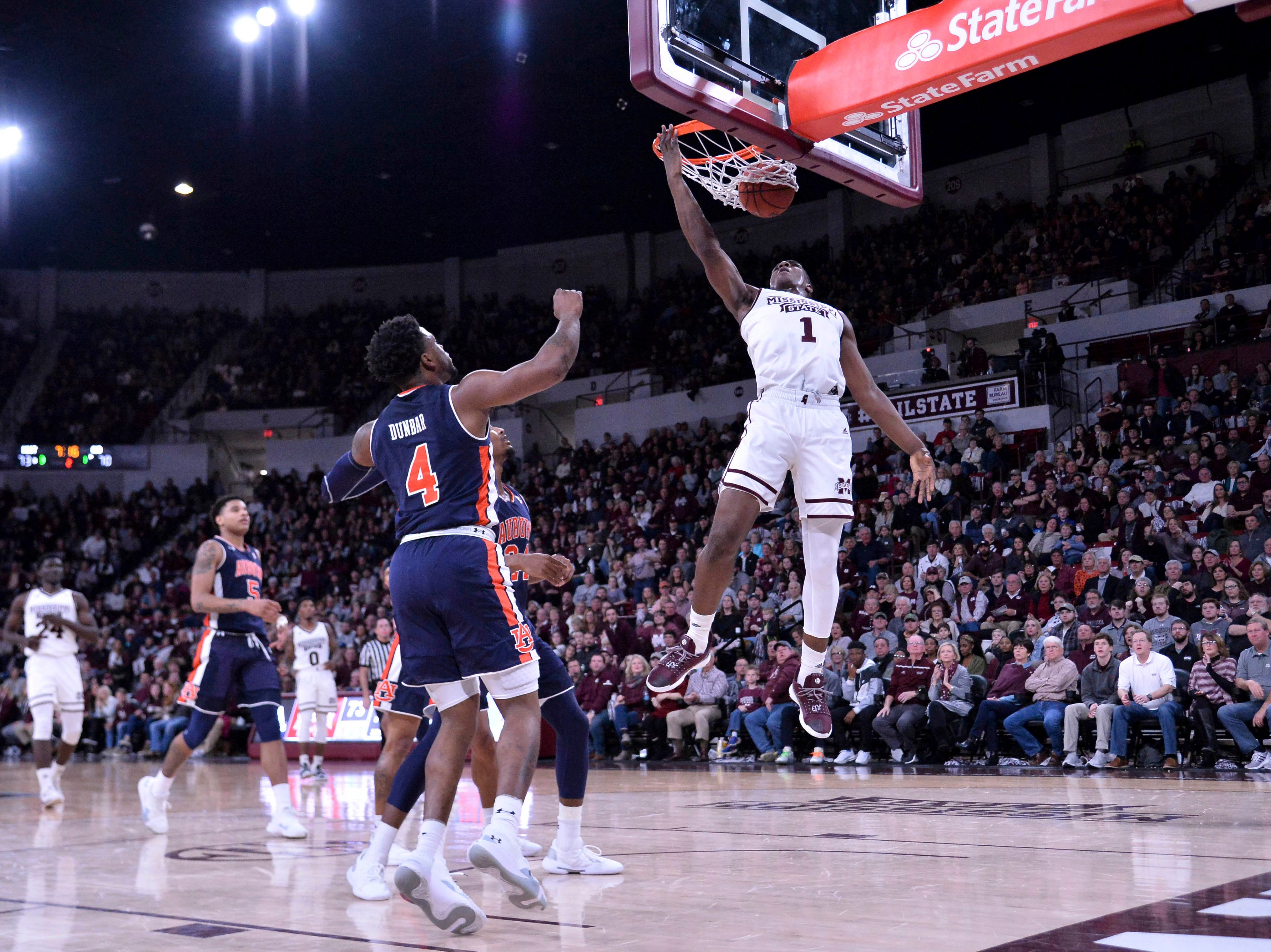 Jan 26, 2019; Starkville, MS, USA; Mississippi State Bulldogs forward Reggie Perry (1) dunks against Auburn Tigers guard Malik Dunbar (4) and forward Anfernee McLemore (24) during the second half at Humphrey Coliseum. Mandatory Credit: Matt Bush-USA TODAY Sports