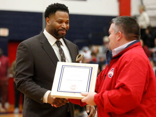 Oakland High School Principal John Marshall hands out a plaque to inductee Gerald King as he is added to the Oakland High School Basketball Hall of Fame on Monday.