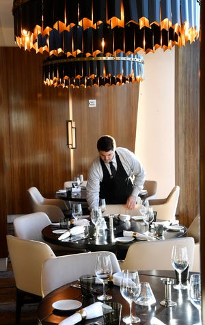 Waiter Geoff Sebold prepares for the night's guests inside Bourbon Steak on the top floor of the JW Marriott which opened in 2018 to a booming hotel market in Nashville Tuesday Jan. 29, 2019, in Nashville, Tenn.