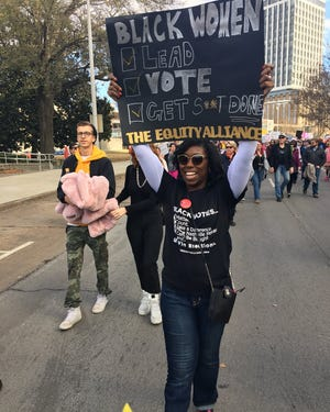 Charlane Oliver, co-founder of the Equity Alliance, holds up a sign during a past Women's March in Nashville.