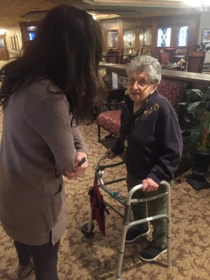 "Lindsey Farrington chats with Inn at Summit Trail resident JoAn Cordi, 104, who served as a ""Rosie the Riveter""-style factory worker during World War II."
