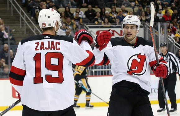 Jan 28, 2019; Pittsburgh, PA, USA; New Jersey Devils center Travis Zajac (19) celebrates after scoring a goal with left wing Miles Wood (44) against the Pittsburgh Penguins during the first period at PPG PAINTS Arena.