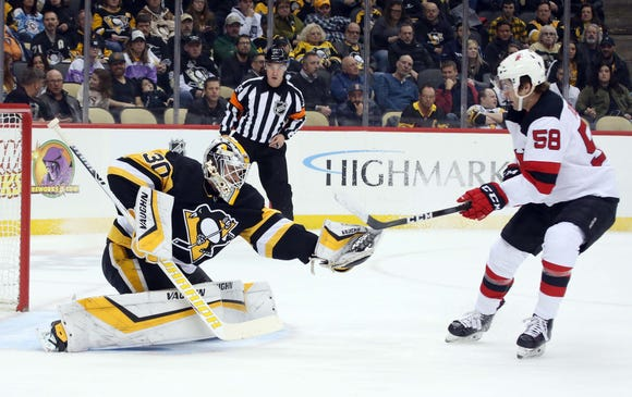 Jan 28, 2019; Pittsburgh, PA, USA; Pittsburgh Penguins goaltender Matt Murray (30) makes a glove save in front of New Jersey Devils center Kevin Rooney (58) during the first period at PPG PAINTS Arena.