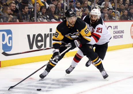 Jan 28, 2019; Pittsburgh, PA, USA; Pittsburgh Penguins defenseman Kris Letang (58) skates with the puck against pressure from New Jersey Devils right wing Kyle Palmieri (21) during the first period at PPG PAINTS Arena.