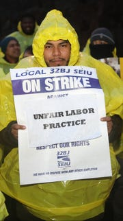 George Castaneda, of North Bergen, a porter and utility worker at the Horizon Housing apartment complex, holds a sign in the cold rain, during a rally in Ft. Lee. Tuesday, January 29, 2019