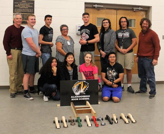 The AHS SHockwave Team and their cars. Also pictured are Holloman High Speed Test Track Engineering Lead John Leslie, standing far left, AHS Shockwave sponsor Colleen Teske, standing at center and HHSTT Senior engineer Kody Sparks standing at far right.