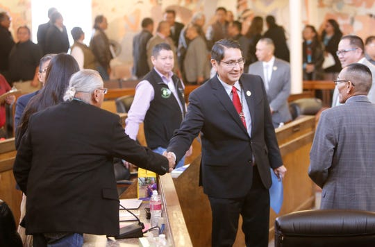 Navajo Nation Council delegates greet tribal President Jonathan Nez, center, before listening to his State of the Nation address during the winter session on Monday at the council chamber in Window Rock, Ariz.