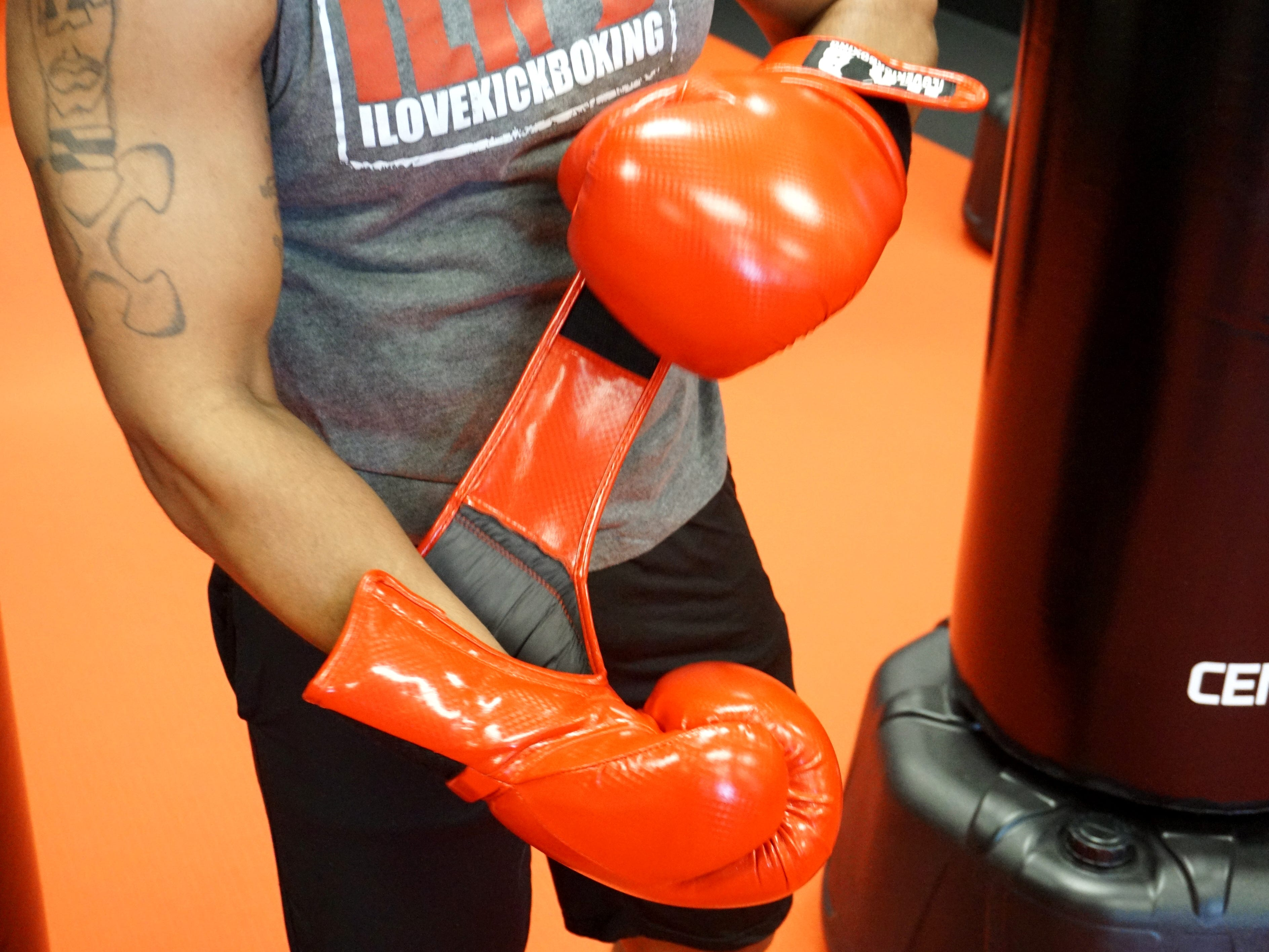 Antonio Green puts his boxing gloves on at the start of a workout. I Love Kickboxing offers an introductory series of three lessons along with boxing gloves for $19.99.