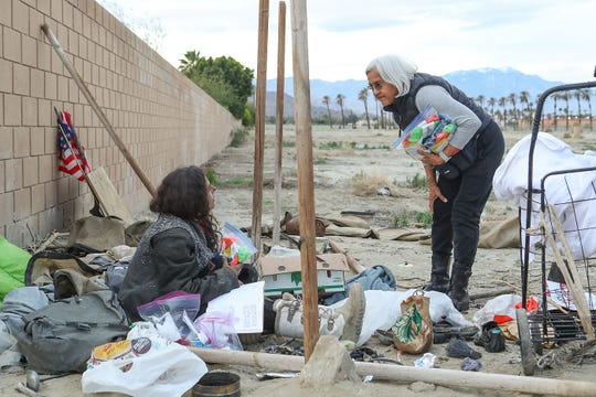Terry Ramon, right, talks with a young homeless woman in Indio during a point-in-time count of homeless people in the Coachella Valley, Jan. 19, 2019.