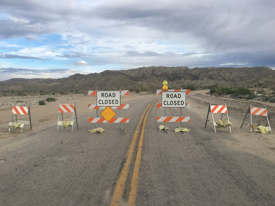 Road signs block Box Canyon Road near Mecca. The road has been closed since October after heavy rain flooded an area between Mecca and Interstate 10.