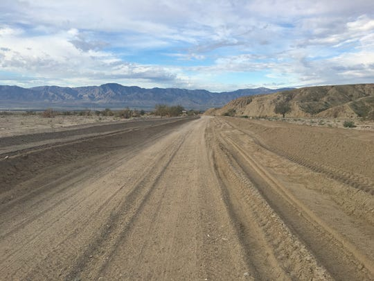 Sand covers Box Canyon Road, which has been closed since October due to flood damage. A $3 million repair project is expected to begin in February.