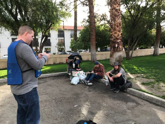 Christopher Gerry, management analyst with the city of Palm Desert, interviews Roger Martin and Robyn Berry as they wait for a recycling center to open during a Point-in-Time homeless count on Tuesday, Jan. 29, 2019, in Palm Desert.