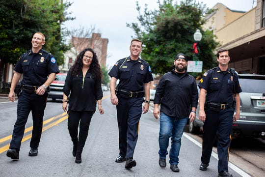 Lisa Long poses with members of the Pensacola Police Department. The police department is a client of the marketing firm Long works as a creative strategist for.