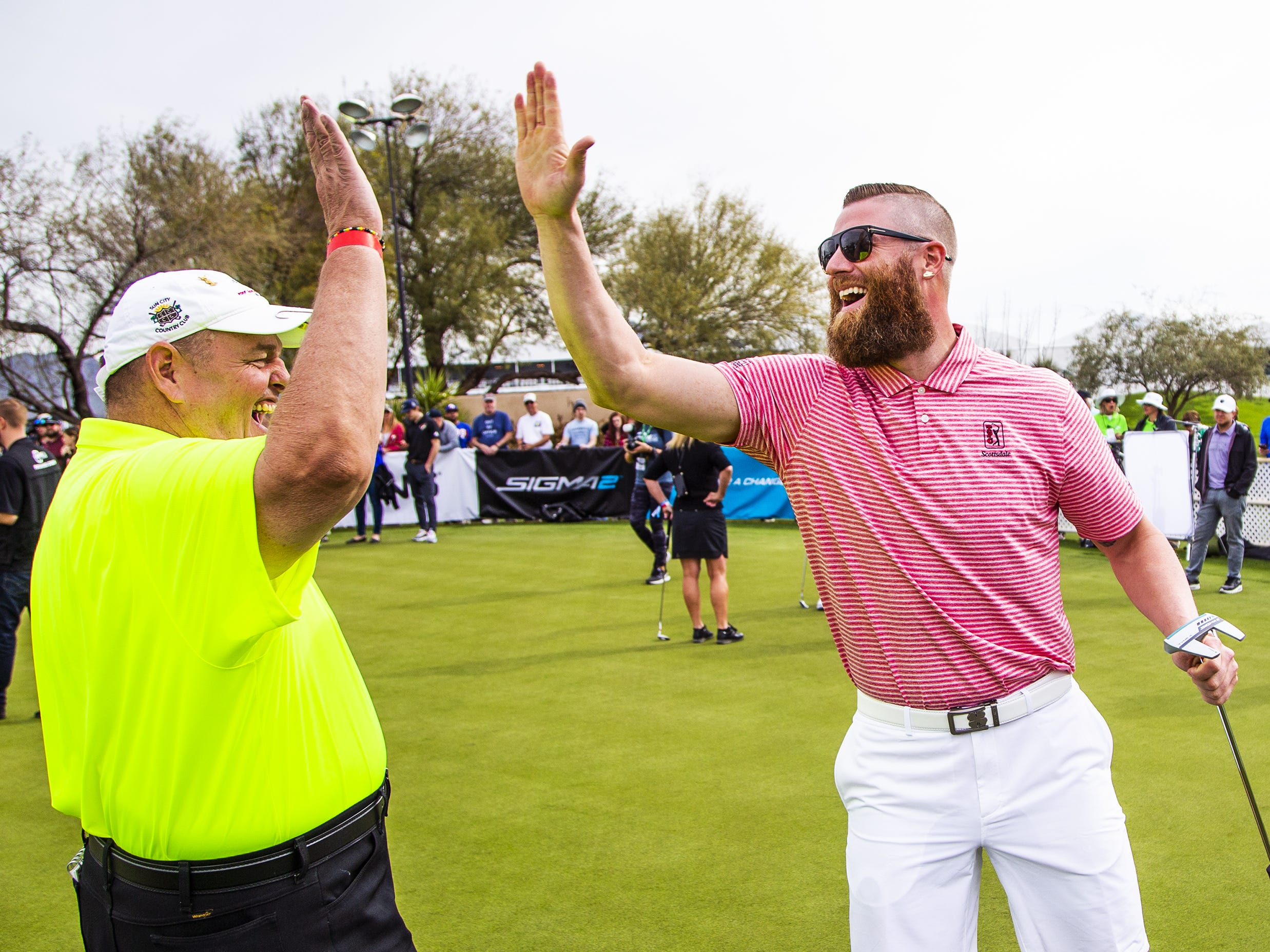 Hans Lentz, left, and his partner, Arizona Diamondbacks pitcher Archie Bradley, high-five during the San Tan Ford Special Olympics Open at the Waste Management Phoenix Open at the TPC Scottsdale, Tuesday, January 29, 2019.
