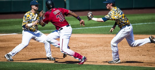 Arizona Diamondbacks Socrates Brito is squeezed by West Virginia University infielders Kyle Davis, left, and Cole Austin at Salt River Fields at Talking Stick, Monday, February 29, 2016. Brito was tagged out. Austin has since transferred to Arizona State.