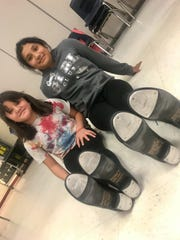 """Two tappers at Sunnyslope School in Phoenix in donated tap shoes that say, """"Donated with love by Brittany"""" on the bottom."""