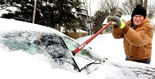 Una mujer trata de desprender el hielo del parabrisas de su vehículo.