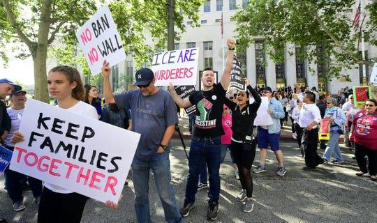 Gente protesta afuera de una corte federal en contra de la política migratoria de Trump.