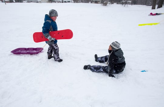 Abram Barrons, 8, left, carries a snowboard and pulls a sled for his friend Cameron Johnson, 7, while he sits n the snow Tuesday, Jan. 29, 2019 on the sledding hill outside Palmer Park Recreation Center. Tuesday was the sixth snow day of the year for many local school districts.