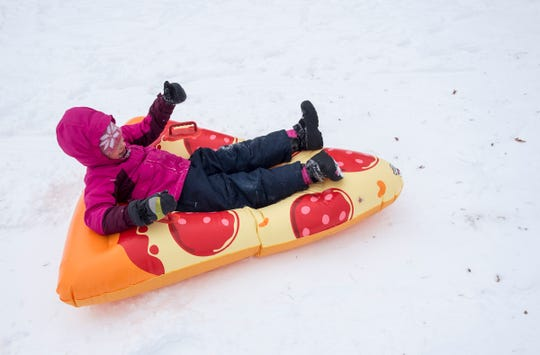 Kenna Nelson, 6, rides an inflatable slice of pizza down the sledding hill outside Palmer Park Recreation Center Tuesday, Jan. 29, 2019. Tuesday was the sixth snow day of the year for many local school districts.