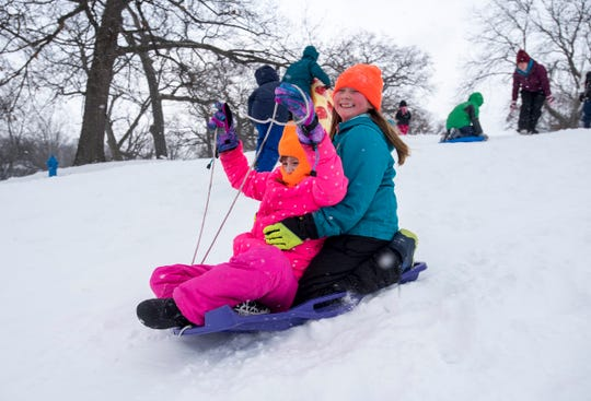 Aarianna Hutchins, 9, right, rides on a plastic sled with her friend Jessie Becker, 8, on Tuesday, Jan. 29, 2019 on the sledding hill outside Palmer Park Recreation Center. Tuesday was the sixth snow day of the year for many local school districts.