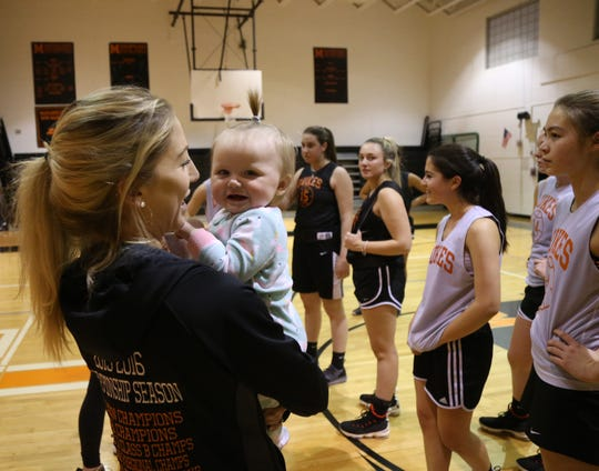Marlboro basketball assistant coach Katelyn Davis holds head coach Marion Casey's daughter Remi during practice at Marlboro High School on January 22, 2019.