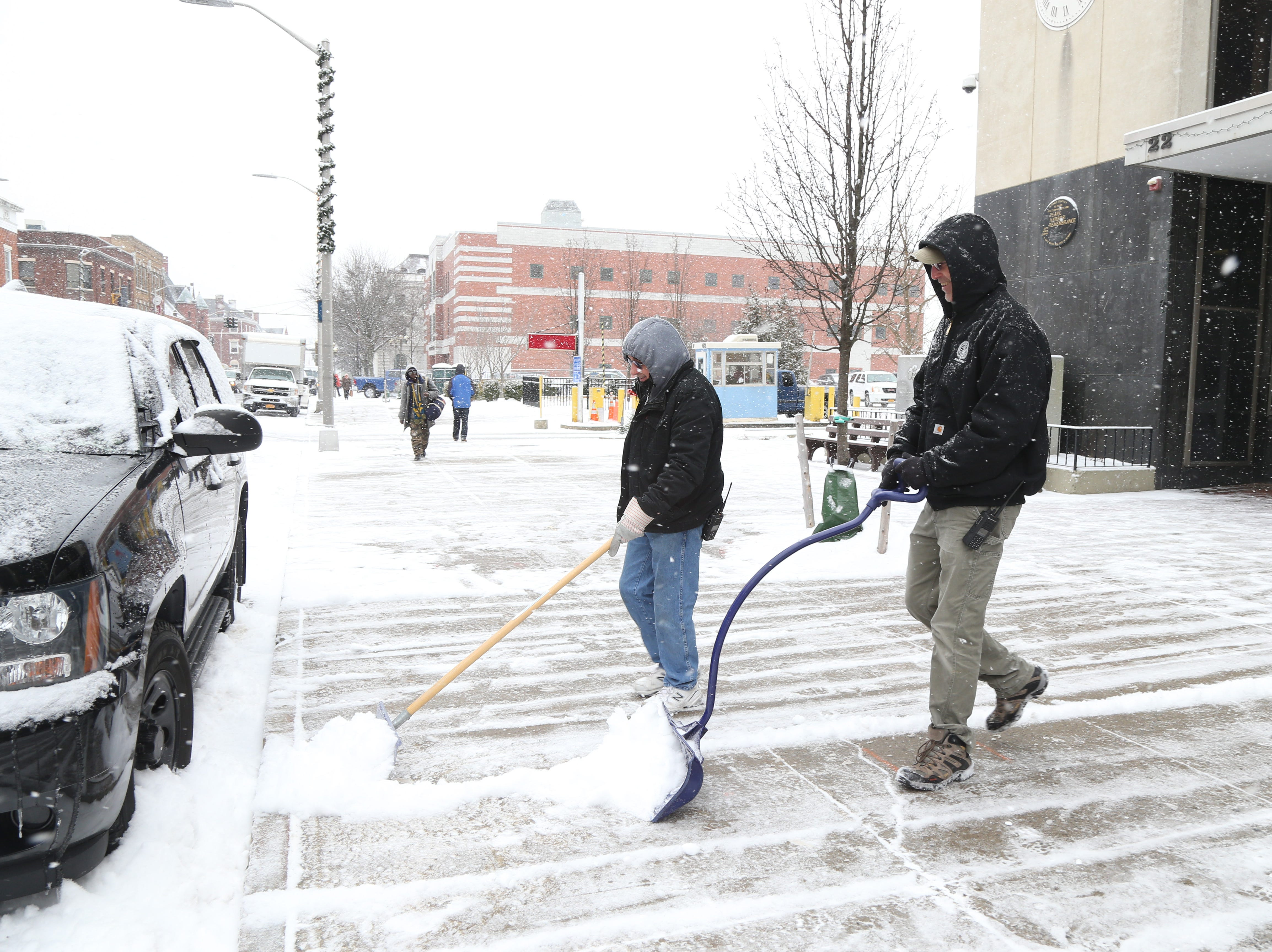 Dutchess County DPW workers, from left, Bernard Murtha and Matt Moran clear the sidewalk outside the Dutchess County Office Building on Market Street in the City of Poughkeepsie on January 29, 2019.