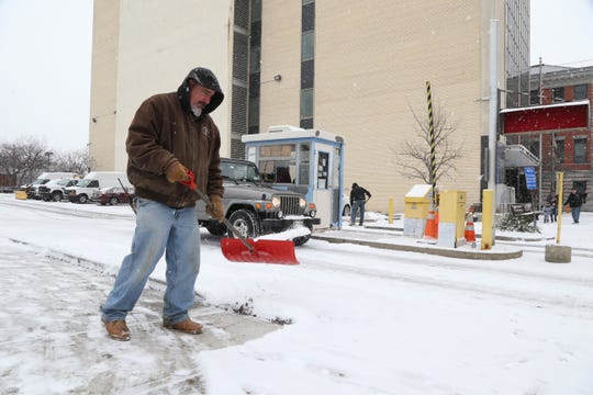 Marc Russette from the Dutchess County DPW clears the sidewalk outside the county parking lot on Market Street in the City of Poughkeepsie on January 29, 2019.