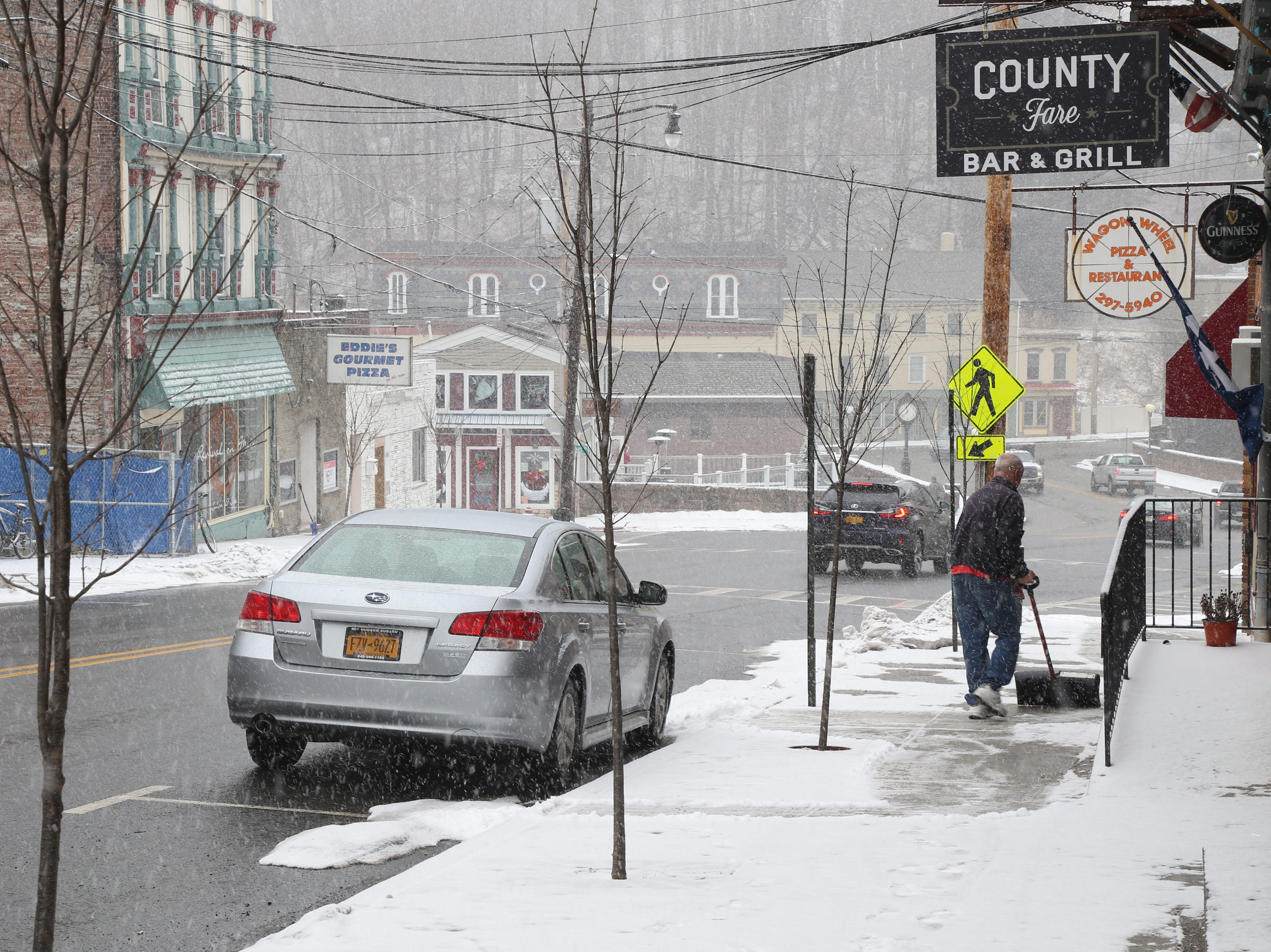 Traffic travels north along East Main Street as shop owners clear the sidewalks in Wappnigers Falls on January 29, 2019.