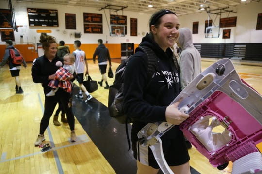 Marlboro's Erin Lofaro carries the baby walker for coach Marion Casey's daughter Remi following practice at Marlboro High School on January 22, 2019.