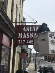 A police officer examines the street sign for Asian Massage, 58 Lincoln Way West, before it was removed Tuesday, Jan. 29, 2019. Police shut down the business, which is being investigated for prostitution.