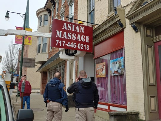 Police watch as a utility worker removes the sign outside Asian Massage, 58 Lincoln Way West, Chambersburg, on Tuesday, Jan. 29, 2019. The business is suspected of engaging in prostitution.