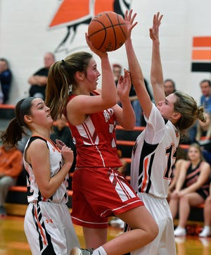 York Suburban's Brooke Sargen, left, and Lulu Mooney, right cover Caroline Hurst of Pequea Valley as she drives the paint, Monday, January 28, 2019.