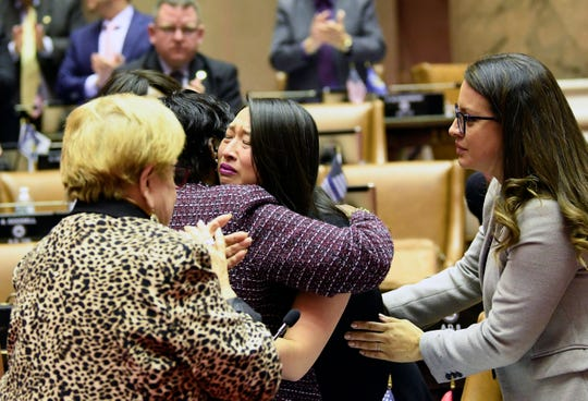 Assemblywoman Yuh-Line Niou, D-Manhattan, center, is hugged by Assemblywoman after Niou, a survivor talked about the sexual abuse she experienced as a child while explaining her vote in the affirmative for the Child Victims Act in the Assembly Chamber at the state Capitol on Monday, Jan. 28, 2019, in Albany, N.Y.